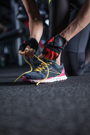 Young woman tying her shoelaces before exercise in gym, closeup Stock Photo