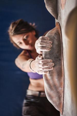 Woman training on practice climbing wall indoor Stock Photo