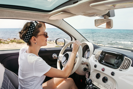 Young woman in car  on sunny day near the sea