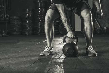 Crossfit kettlebell training in gym. Athlete doing crossfit workout