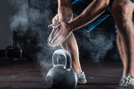 Sports background. Young athlete getting ready for weight lifting training. Powerlifter hand in talc preparing to training Stock Photo