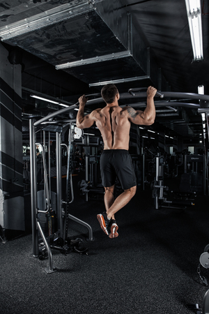 Back view of muscular man doing pull up exercise