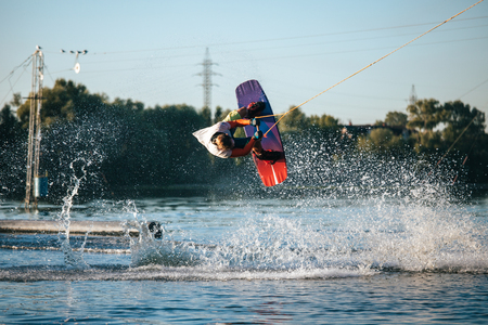 Wakeboarder makes an extreme jump. Sport and active lifestyle.