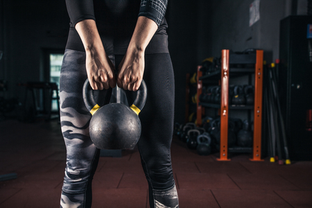 Kettlebell training in gym. Woman doing workout