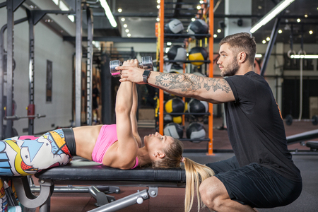 Personal trainer helping woman working with heavy dumbbells Stock Photo