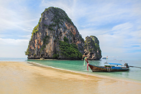 Long tail boat on tropical beach with rock on background