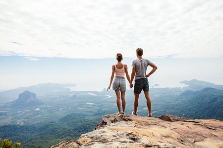 Viajeros de la joven pareja relajándose en la cima de una montaña y disfrutando de la vista. Concepto de viaje.