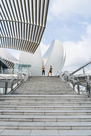 fitness, sport, people, exercising and lifestyle concept - couple relaxing  on city stairs