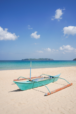 A small blue boat on a tropical beach