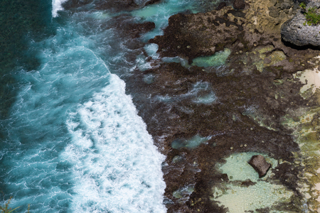Epic aerial view of blue ocean waves crashing into rocky coast Stok Fotoğraf