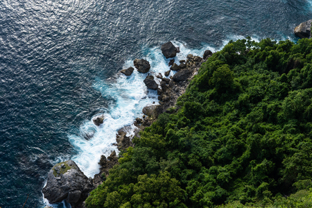 Waves on beautiful sea rocky coastline with green trees, aerial view Stok Fotoğraf