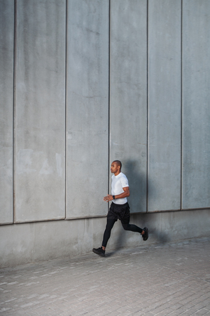 Man running in the urban space with  concrete wall on background. Healthy lifestyle