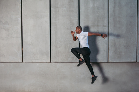 Athlete running against concrete wall. Man sprinting on the street