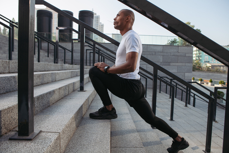 Athletic runner doing stretching exercise, preparing for morning workout
