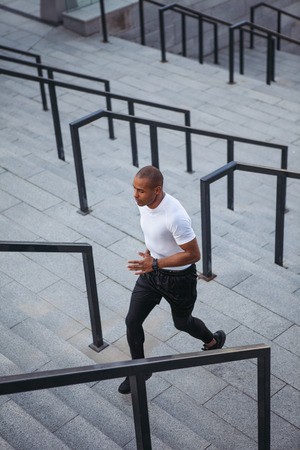 Portrait of sportsman running up stairs