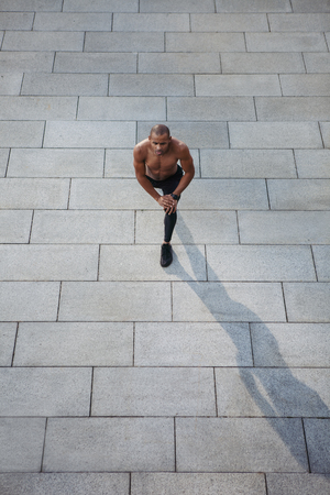 Training on fresh air. Handsome young man doing stretching exercises before running while standing outdoors