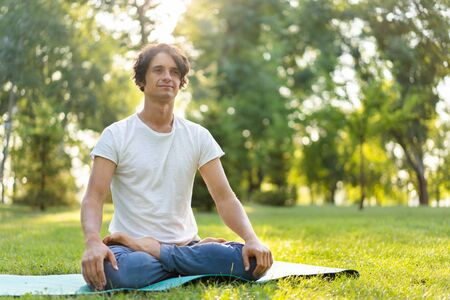 Young man meditating outdoors in the park 스톡 콘텐츠 - 132118222