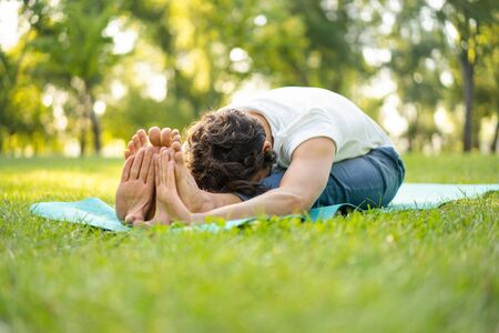 Man practicing  yoga in the park. Yoga exercises. 스톡 콘텐츠 - 132116140