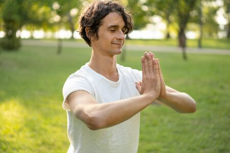 Young man meditating outdoors in the park 스톡 콘텐츠