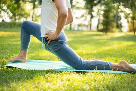 Man practicing  yoga in the park. Yoga exercises.