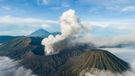 Crater with active volcano smoke in East Jawa, Indonesia. Aerial view of volcano crater Mount Gunung Bromo is an active volcano