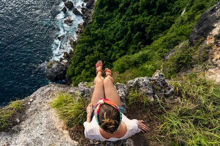 Girl sitting on the cliff