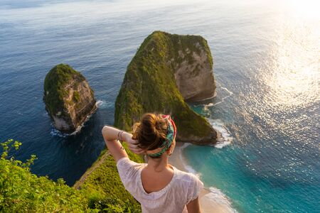 Woman standing on the cliff and enjoying sunset. Kelingking Beach at Nusa Penida, Bali