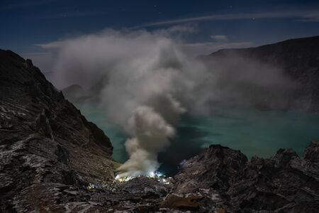 Ijen volcano crater and sulphur mining at the night. East Java, Indonesia