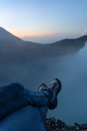 Adventure seeker sitting on the cliff and enjoying the view of acid lake in Ijen volcano crater at sunrise Stock Photo