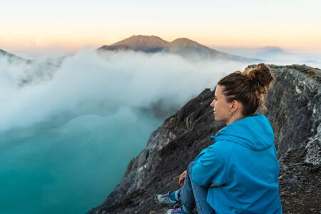 Backpacking in Asia, looking for dreamscape. Woman sitting on a cliff above volcano Kawah Ijen crater.