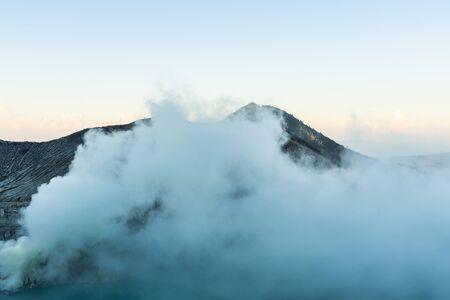 Beautiful Landscape mountain and blue lake with smoke sulfur in the morning in a Kawah Ijen volcano. Stock Photo