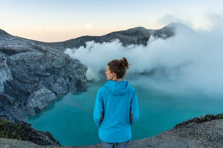 Backpacking in Asia, looking for dreamscape. Woman standing on cliff above volcano Kawah Ijen crater.
