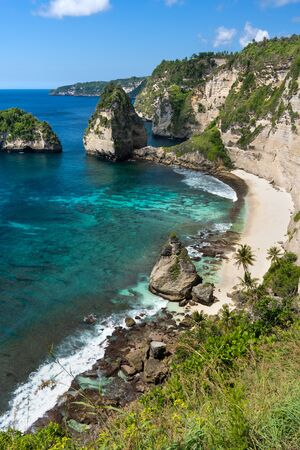 Turquoise tropical bay surrounded by cliffs. Nusa Penida, Bali, Indonesia