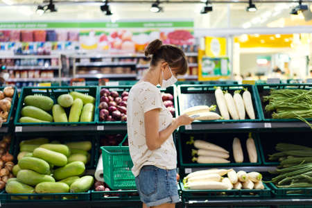 Young woman with face mask using mobile phone and buying groceri