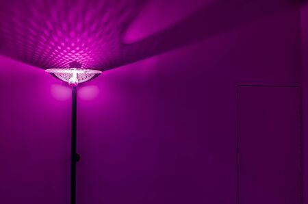 Die Lampe in einem leeren Raum mit dem mitgelieferten Licht. Abstraktes Foto mit einer brennenden Lampe in einem leeren Raum. Hintergrundbild.