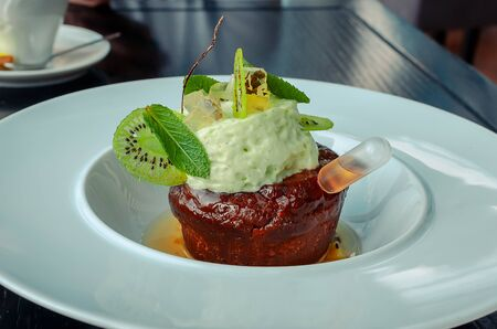 Chocolate cake with cognac in the restaurant. The cupcake is decorated with a soufflé of kiwi, mint leaves and fruit jelly