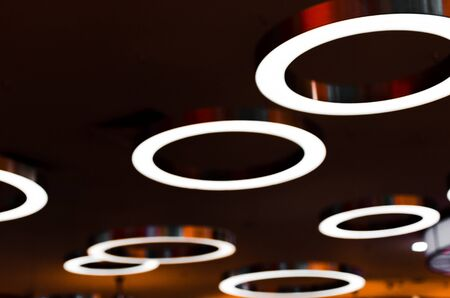 Fixtures in the unfocus in the form of large rings with a bright light. Background picture of luminous lamps