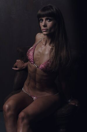 Girl bodybuilder in a swimsuit closeup posing in a photo studio. A girl showing a trained body shape. Low key style photo Standard-Bild