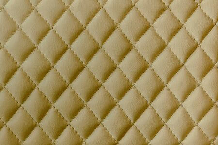 Leather texture background. Yellow leather stitched with threads.