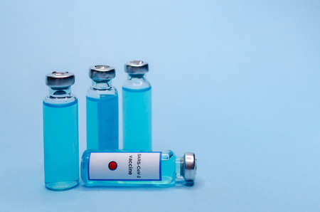 Coronavirus vaccine in glass vials on a blue background Stock Photo