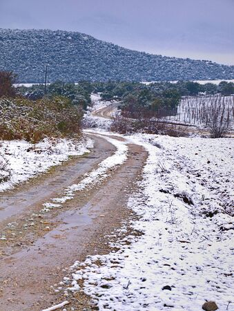 Dirt road with mud on snow covered landscape, Pieria, Greece. 写真素材