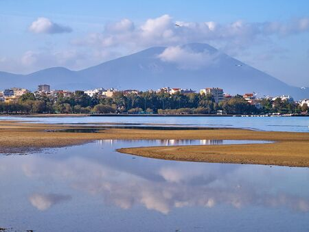 Mountain and sky reflection on sea water during low tide, Liani Ammos in Chalkida, Greece.