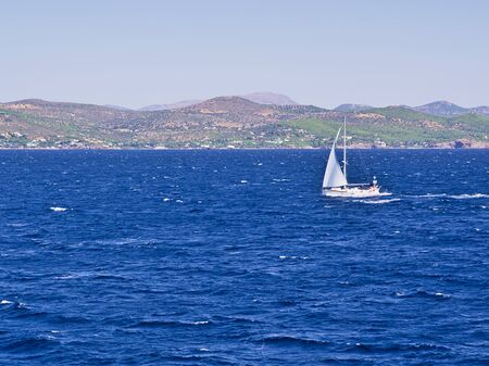 Sailboat at Aegean sea, background with island hills.