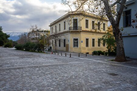 Athens, Greece, early morning in Dionysiou Areopagitou street under acropolis hill in winter. Neoclassical buildings,  bare trees and  paved road under cloudy sky.
