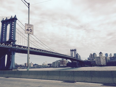 Manhattan bridge and the speed limit sign opposite the city in vintage style