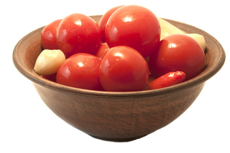 the pickled tomatoes are in a clay dish on a white background photo