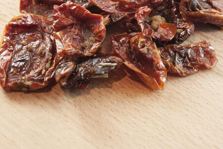 Dried slices of tomato on a brown board photo