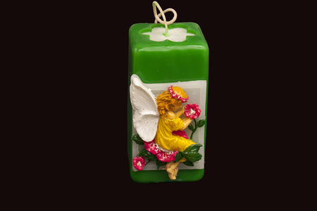 paraffin: one paraffin square green candle with the  angel. on black background. Handmade