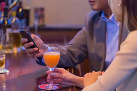 通信: バーのカウンターでスマート フォンを使用して日本のカップル