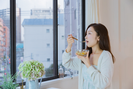 nightwear: Lady in nightwear eating cereals Stock Photo